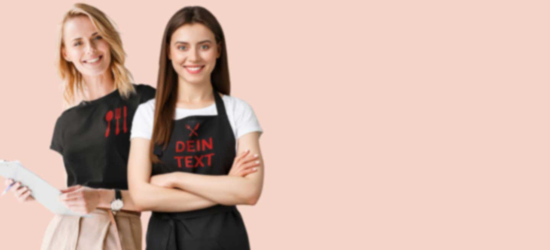 Zwei Kellnerinnen in T-Shirt und Schürze mit Firmenlogo